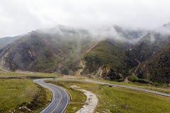 云彩、青山和白色汽车的弯曲的山路 库存图片