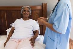 互动与女性医生的资深妇女在卧室 图库摄影