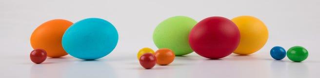 五颜六色的复活节彩蛋在白色背景,大和小鸡蛋的横幅 免版税库存图片