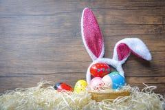 五颜六色的复活节彩蛋和复活节兔子耳朵兔子在篮子巢装饰木背景中 免版税图库摄影