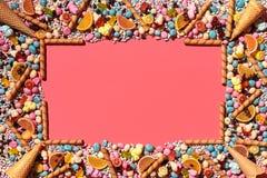 以在珊瑚背景的一个框架的形式多彩多姿的给上釉的糖衣杏仁和其他甜点被安排 库存图片