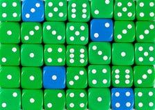 任意被定购的绿色背景切成小方块与四个蓝色立方体 免版税库存照片