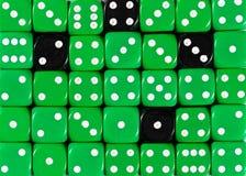 任意被定购的绿色背景切成小方块与四个黑立方体 库存照片