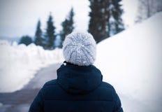 从令人惊讶的女孩后面的画象在寒冷冬天天 一年轻女人的室外照片看在距离的羊毛灰色帽子的 免版税库存图片