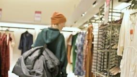 从后面女孩购物的看法在一件毛线衣和帽子步行通过服装店 活照相机 股票录像