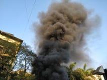 从在火的黑烟一个大厦出来 免版税库存照片