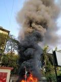 从在火的黑烟一个大厦出来 免版税库存图片
