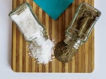 从玻璃盐瓶和胡椒振动器和胡椒驱散的盐在一个切板 库存照片