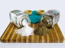 从玻璃盐瓶和胡椒振动器和胡椒驱散的盐在一个切板 免版税库存图片