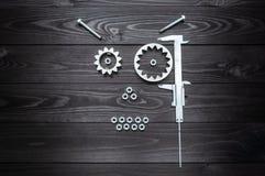 从齿轮工具和坚果的机器人面孔在木背景 免版税库存照片