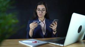 付与信用卡和智能手机,网络购物,生活方式技术的妇女网上付款 女孩进入银行 股票录像