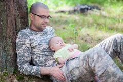 伪装制服的父亲和他的婴孩 免版税库存照片