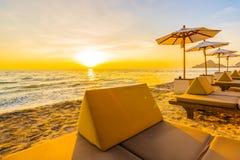 伞和椅子与枕头在海滩和海附近美好的风景  库存图片