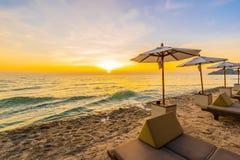 伞和椅子与枕头在海滩和海附近美好的风景  免版税库存照片