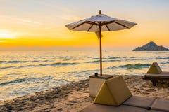 伞和椅子与枕头在海滩和海附近美好的风景  免版税库存图片