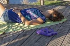 休息的观点的女孩说谎在与蓝色海滩拖鞋的毛巾在眺望台,在河的木结构 免版税库存照片