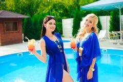 休息由有鸡尾酒的游泳场的两个愉快的女孩 免版税库存照片