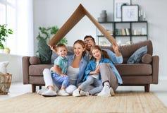 住房和拆迁的概念 幸福家庭母亲父亲和孩子与屋顶在家 免版税图库摄影
