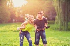 使用与他们的孩子的愉快的童年父母在公园 免版税库存照片