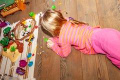 使用与许多的女孩孩子在木地板上的五颜六色的塑料玩具户内 图库摄影