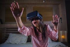 使用与虚拟现实VR风镜耳机设备的愉快和激动的女孩获得在有的床上的乐趣3D与录影的经验 库存图片
