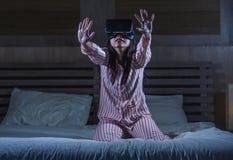 使用与虚拟现实VR风镜耳机设备的愉快和激动的女孩获得在有的床上的乐趣3D与录影的经验 库存照片