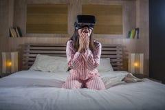 使用与虚拟现实VR风镜耳机设备的愉快和激动的妇女获得在有的床上的乐趣3D与录影的经验 库存照片