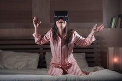 使用与虚拟现实VR风镜耳机设备的愉快和激动的妇女获得在有的床上的乐趣3D与录影的经验 免版税库存图片