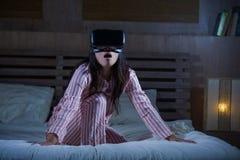 使用与虚拟现实VR风镜耳机设备的愉快和激动的妇女获得在有的床上的乐趣3D与录影的经验 免版税库存照片