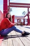 使用一个手机时,穿都市衣裳的愉快的美丽的年轻女人侧视图坐地面和看照相机,当 免版税图库摄影