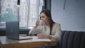 使用她的膝上型计算机的被集中的妇女坐在桌在咖啡馆 女孩坐沙发在窗口饮用的咖啡附近 股票录像