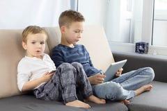 使用小配件的两个孩子在家 有片剂计算机的兄弟在轻的屋子里 打在平板电脑的男孩比赛,情感 免版税库存图片