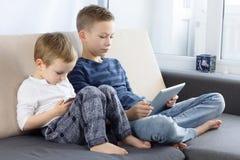 使用平板电脑和smartphon的两个孩子在家 有片剂计算机的兄弟在轻的屋子里 打在片剂计算机上的男孩比赛 免版税库存照片