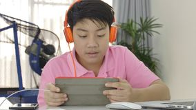 使用在有橙色耳机的片剂计算机上的愉快的亚裔男孩, 股票录像