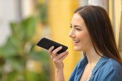 使用在电话的女孩语音识别在一条五颜六色的街道 免版税图库摄影
