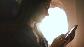 使用在飞机飞行,阳光的年轻愉快的女实业家惊人的特写镜头射击智能手机锐化通过窗口 股票录像