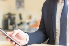 使用流动智能手机的人坐的一会儿 工作在电话的确信的企业家 免版税库存图片