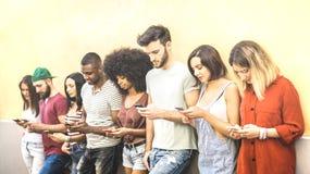 使用流动智能手机的多种族朋友在大学coampus -智能手机使上瘾的Millenial人-技术概念 免版税库存图片