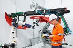 使用测量工具的工程师检查产业机器人夹子汽车制件,聪明的工厂概念 免版税库存图片