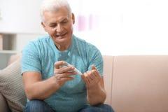 使用柳叶刀笔的老人在家 免版税库存照片