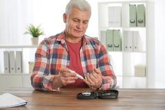 使用柳叶刀笔的老人在桌上 Diabete 库存照片
