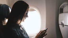 使用智能手机移动式办公室应用程序的特写镜头美丽的轻松的白种人年轻愉快的女实业家在平面飞行期间 股票视频