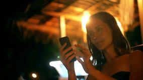 使用智能手机移动式办公室应用程序,照相机在夜休息室咖啡馆椅子的轻松的愉快的年轻成功的妇女掀动  股票录像