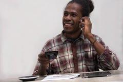 使用智能手机的一个愉快的黑人在家 微笑的年轻非洲人在家坐长沙发,当喝咖啡时 库存照片