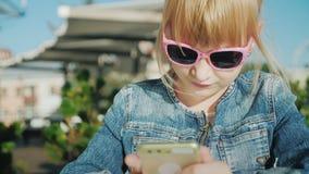 使用智能手机的一个白肤金发的女孩的画象 坐在咖啡馆的一个夏天大阳台 明亮的晴朗的暑假天 股票录像