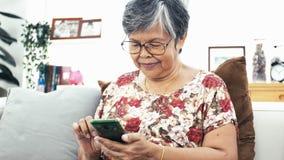 使用智能手机的亚裔资深妇女和在家喝一杯咖啡 股票视频