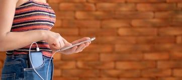 使用智能手机的妇女,当充电在力量银行时 免版税图库摄影