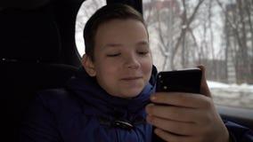 使用智能手机的年轻男孩在出租汽车乘驾期间在城市 股票录像