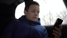 使用智能手机的年轻男孩在出租汽车乘驾期间在城市 影视素材
