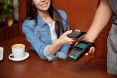 使用终端的妇女为与智能手机的不接触的付款在咖啡馆 免版税库存照片